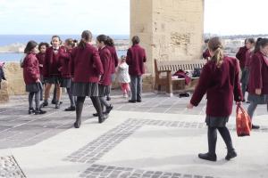 valletta-malta-children-girls-from-church-school-play-with-street-birds-pig_bkfmukqsl_thumbnail-full01